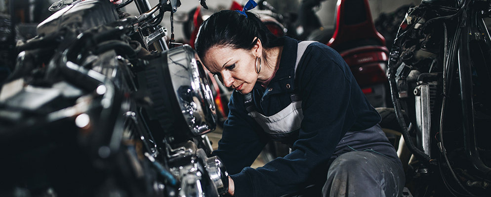 woman working on car