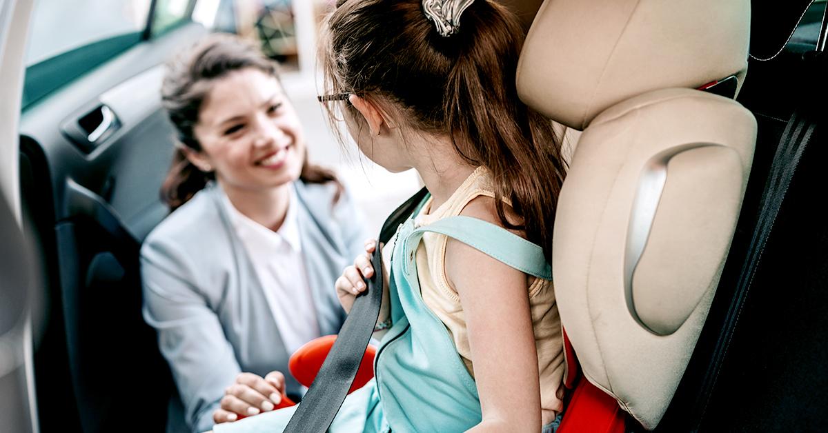 Woman buckling daughter into car